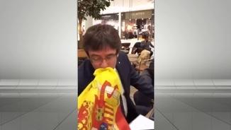 Puigdemont en el moment de fer el petó a la bandera espanyola