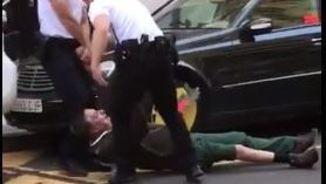 Agents enretirant de la calçada l'home estirat a terra
