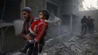 Un home amb un nen als braços després d'un dels atacs aeris a Guta (Reuters)
