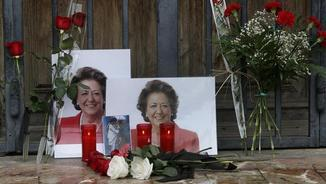 Fotografies i flors col·locades davant d'una de les portes de l'Ajuntament de València (EFE)