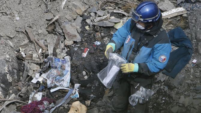Un membre de l'equip de recerca recollint restes de l'avió (Reuters)