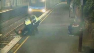 Moment en què els quatre homes aconsegueixen salvar la dona instants abans de l'arribada del tren