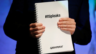 Un membre de Greenpeace mostra un exemplar dels documents (Reuters)