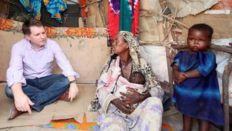 Justin Forsyth parlant amb una dona somali en un camp de refugiats l'any 2012 (Reuters)