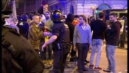 Un mosso saludant un manifestant ultra a la plaça Artós de Barcelona